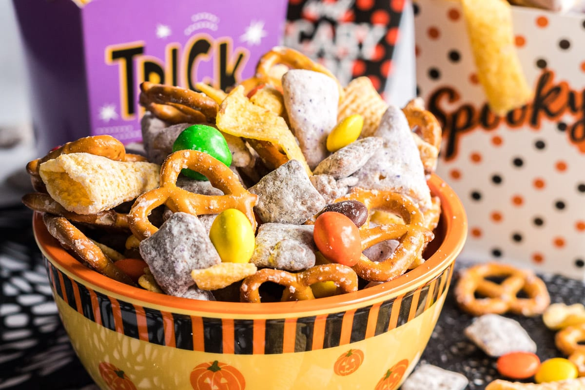 Snack mix in an orange bowl.
