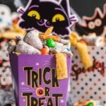 Snack mix in a purple paper cup decorated for halloween.