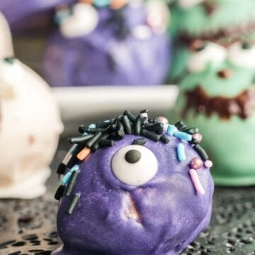 Peanut butter ball coated in purple chocolate with candy eye and sprinkles.