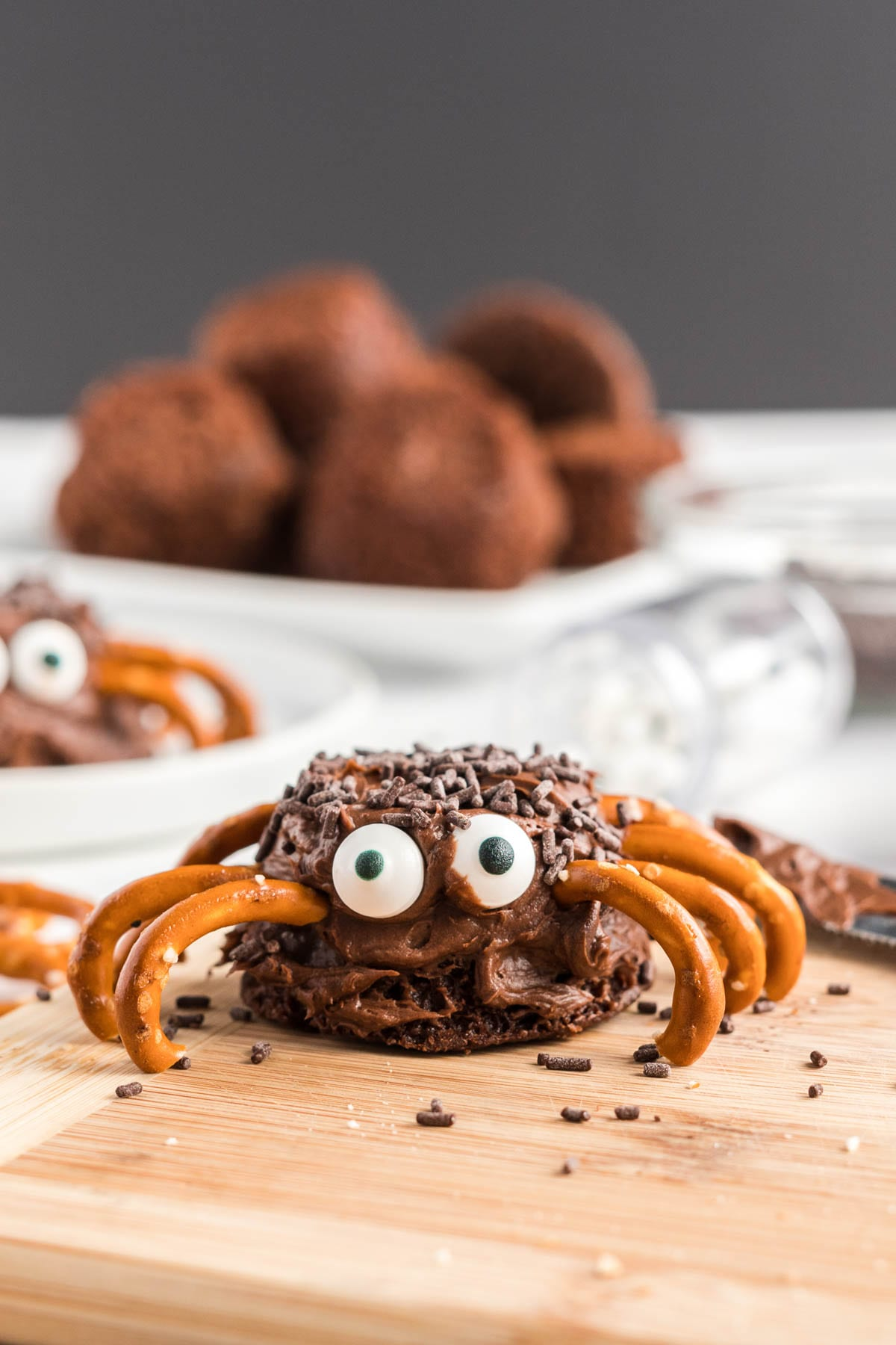 Close up of finished spider with frosted brownie, candy eyes and pretzel legs.