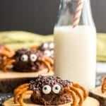 Spider brownie on wooden plate with bottle of milk.