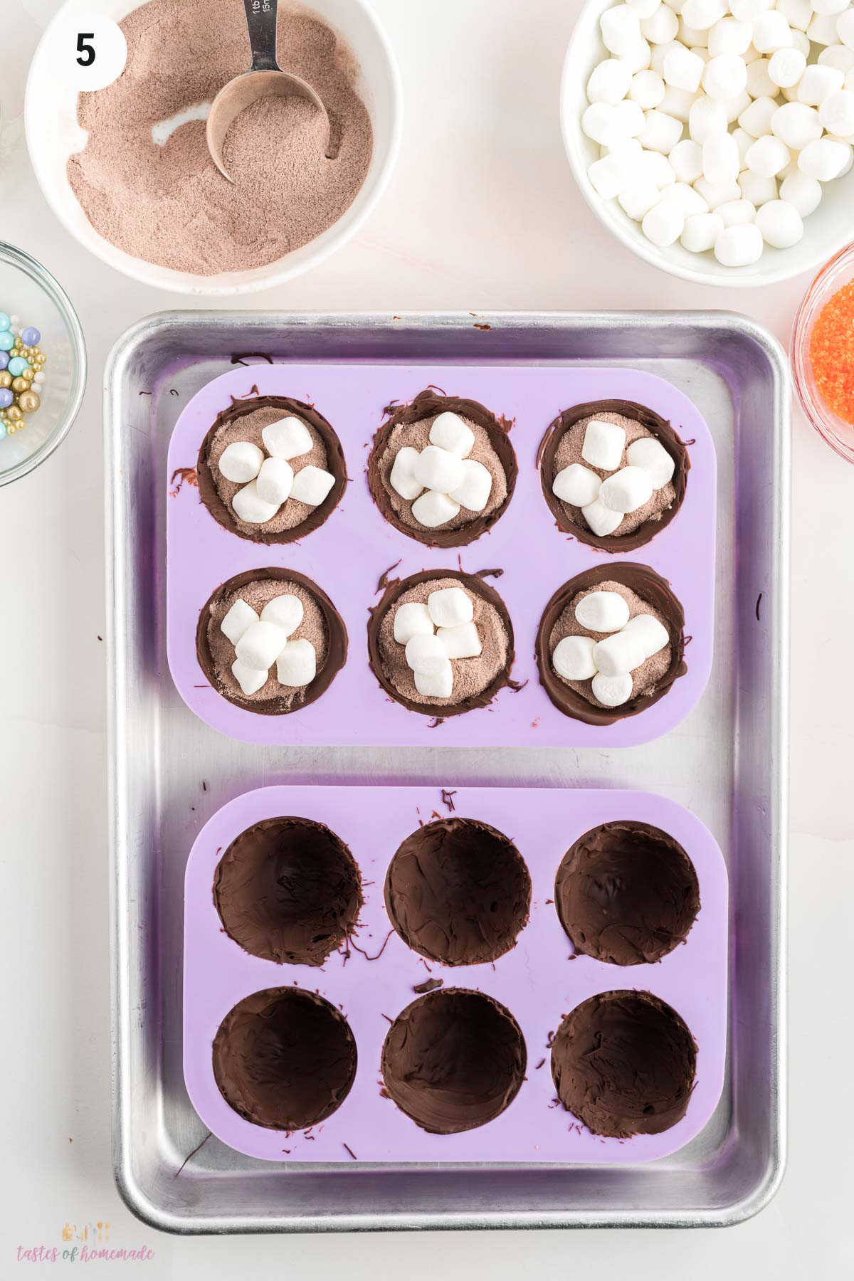 Six chocolate molds filled with hot chocolate mix and marshmallows and six empty halves.