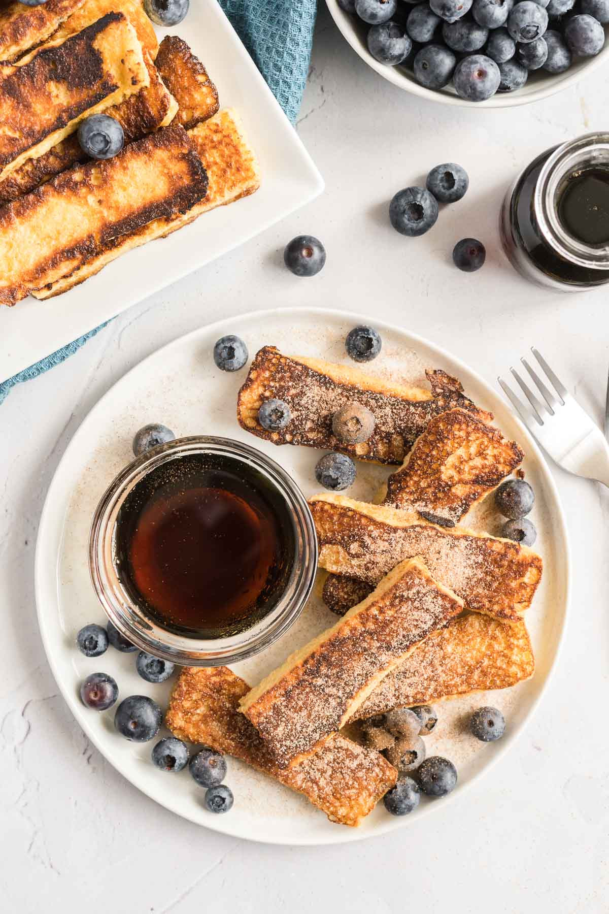 French toast sticks on a plate with cinnamon sugar, blueberries and syrup.