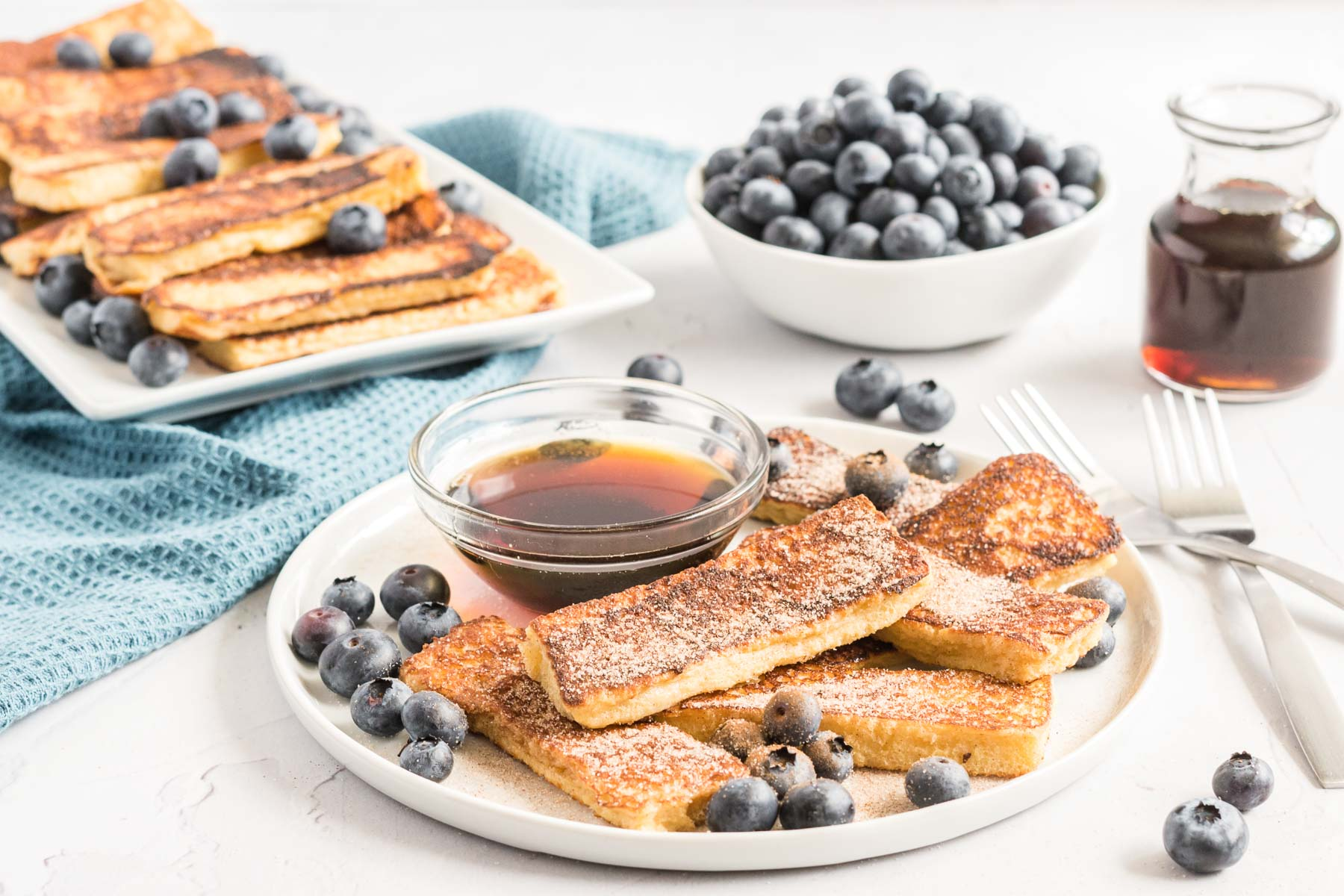 French toast sticks on a plate with a dish of syrup and fresh blueberries.