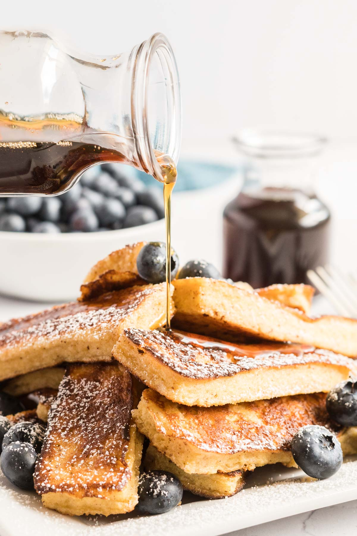 Pouring syrup on a stack of French toast.