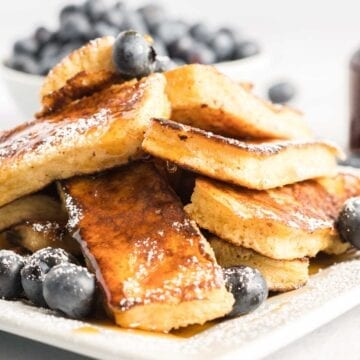 Stack of French toast drenched in syrup.