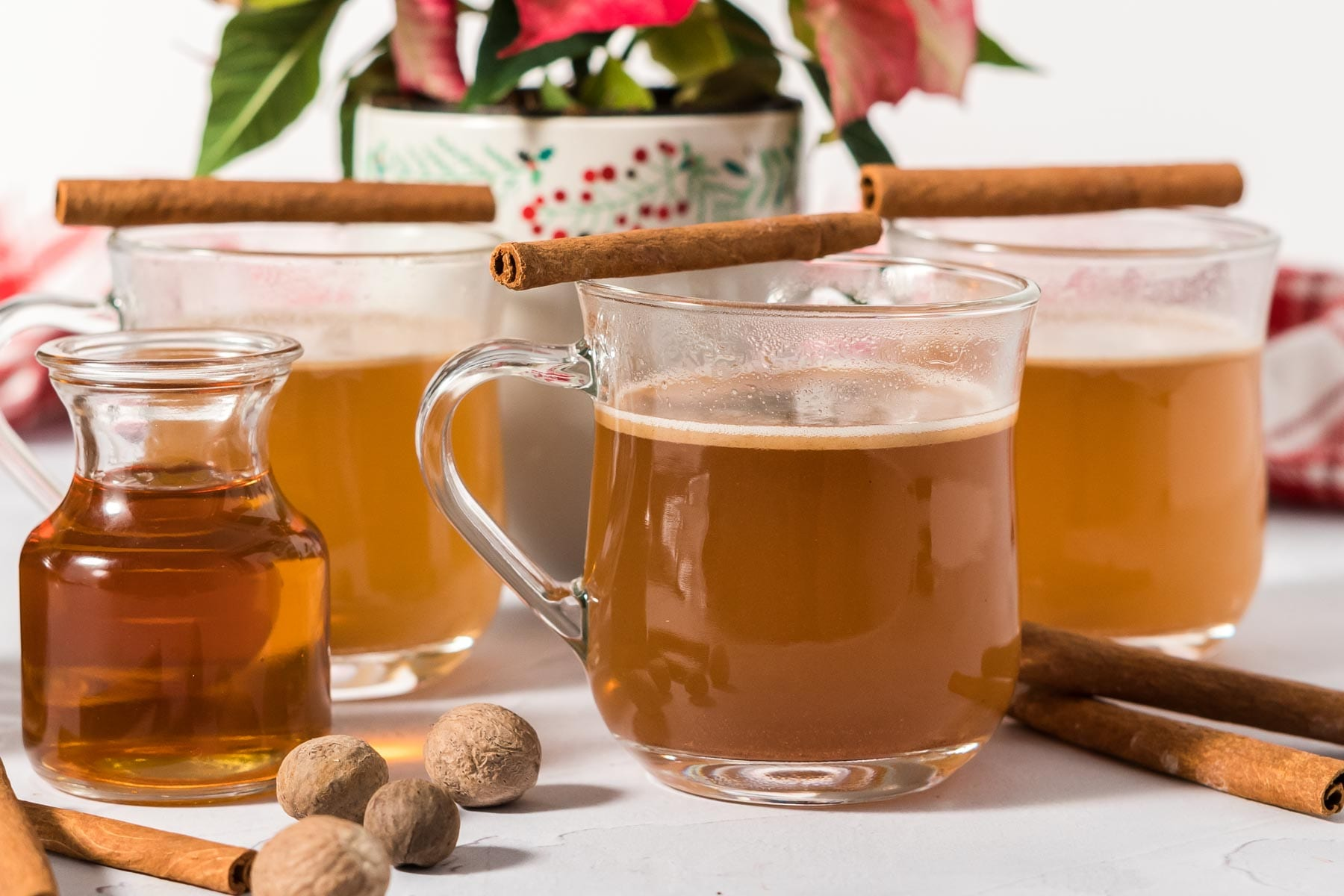 Hot buttered rum in mugs with a bottle of rum garnished with nutmeg and cinnamon.