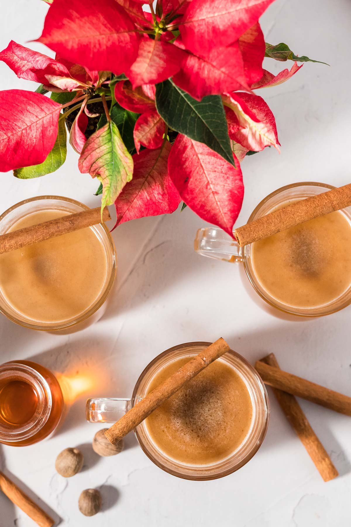 Overhead view of hot buttered rum in mugs garnished with cinnamon sticks beside a poinsettia.