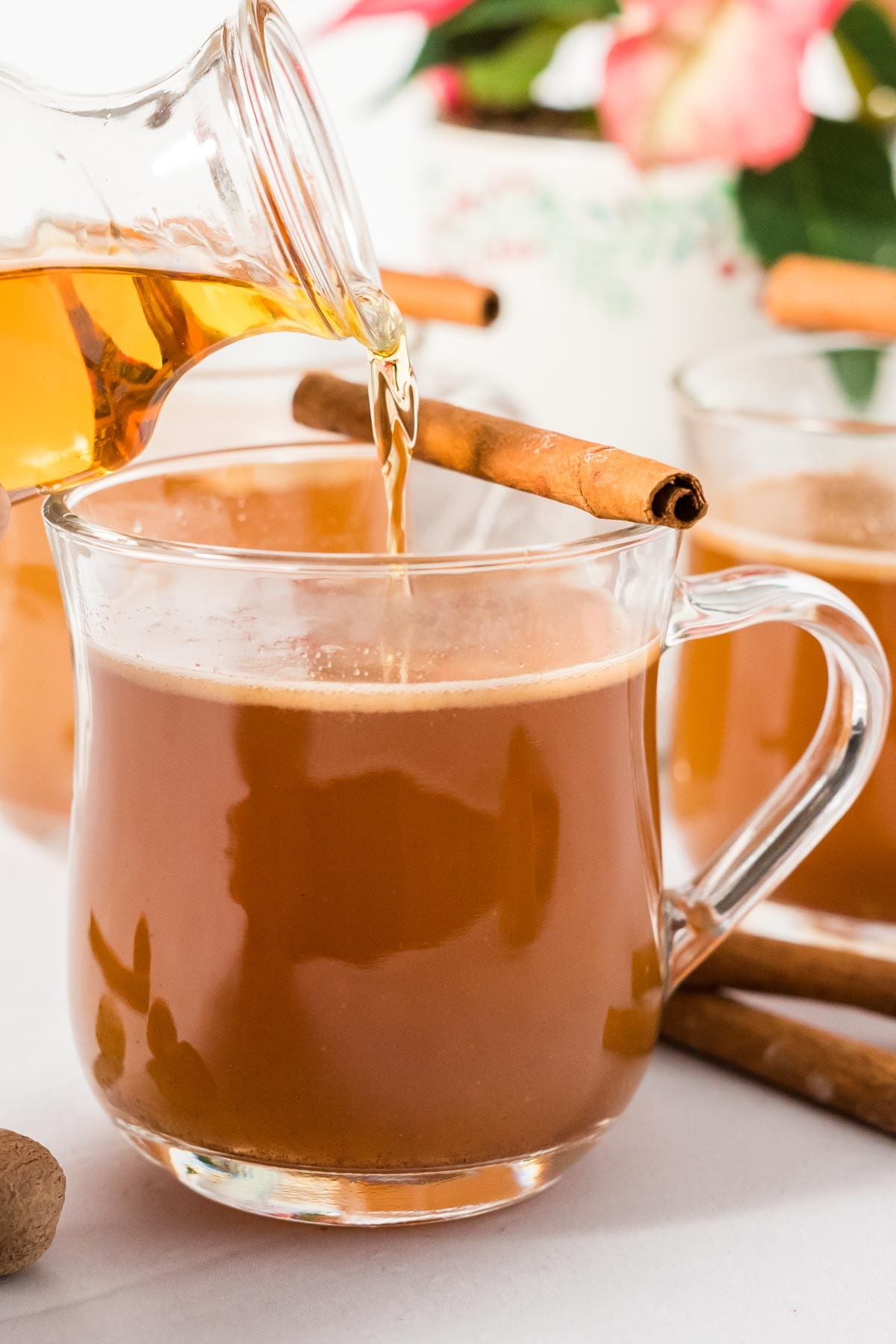 Rum being poured into a mug of hot buttered rum mix.