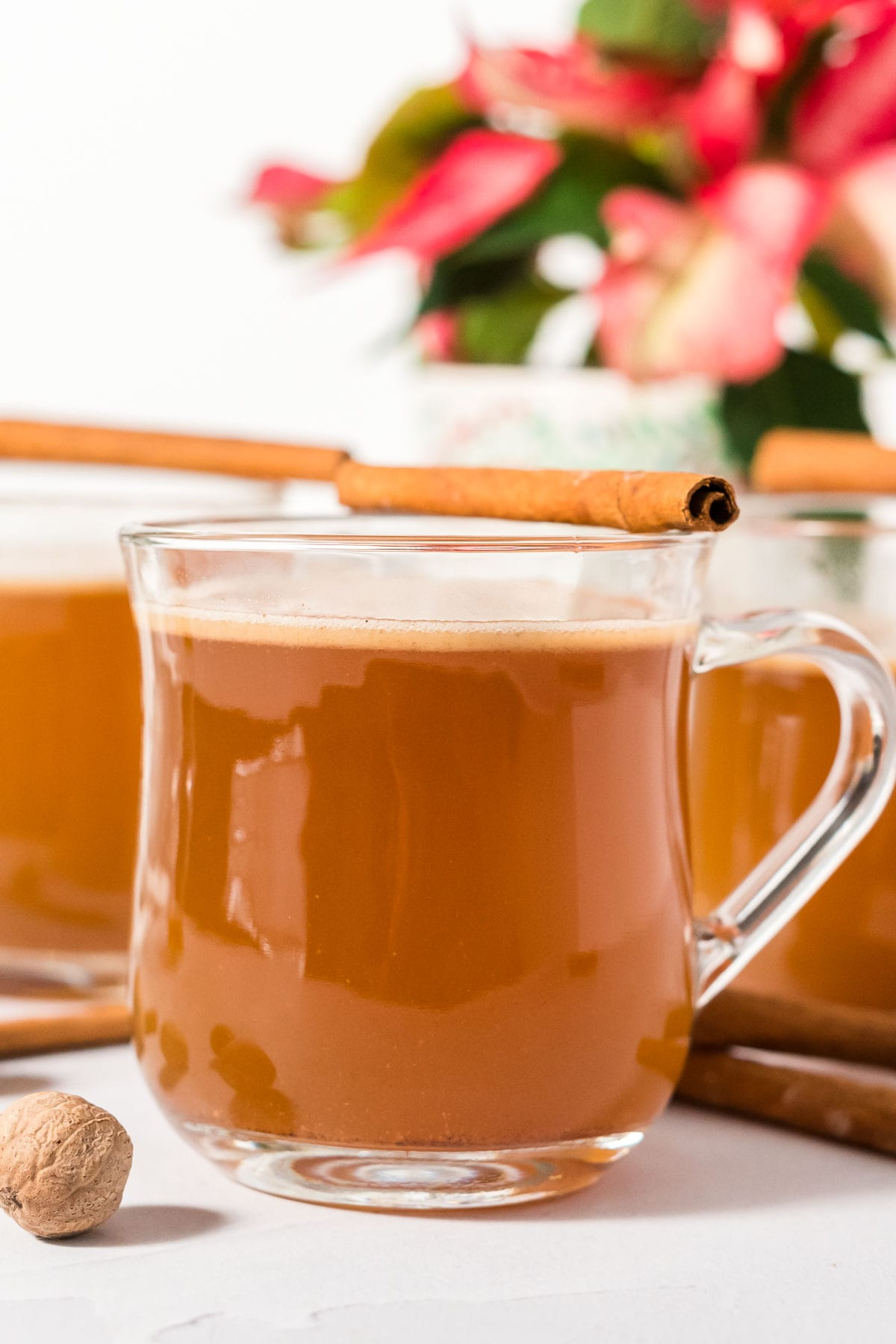 Three mugs of hot buttered rum garnished with cinnamon sticks.