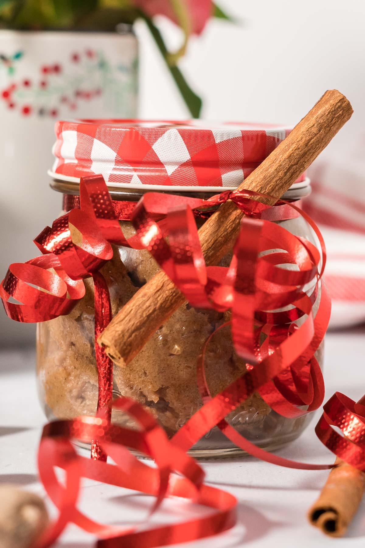 Hot buttered rum mix in a jar decorated with cinnamon sticks and curly red ribbon.