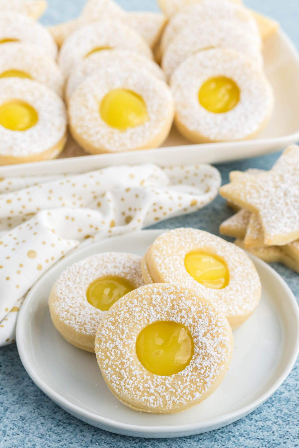 Lemon curd shortbread on a plate with a platter of cookies in the background.