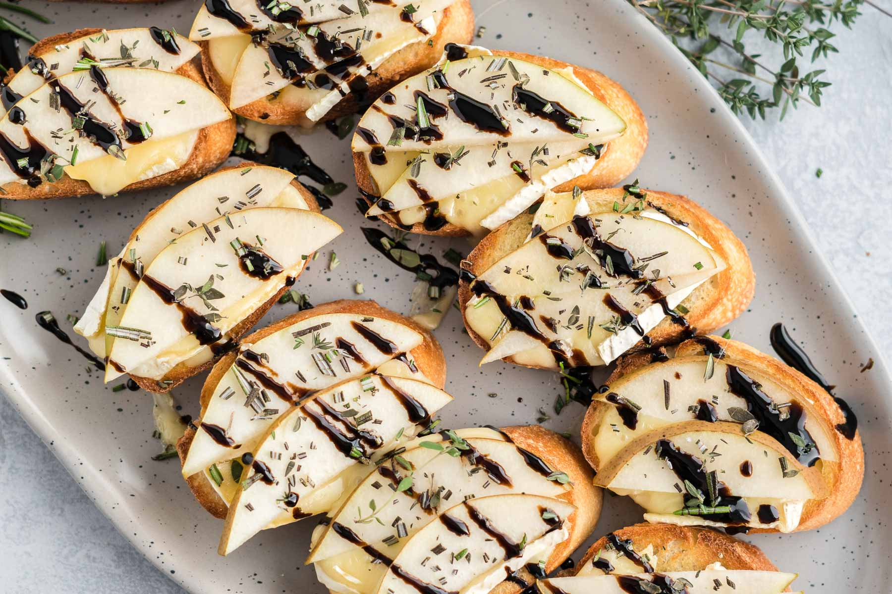 Platter of crostini with balsamic drizzle.