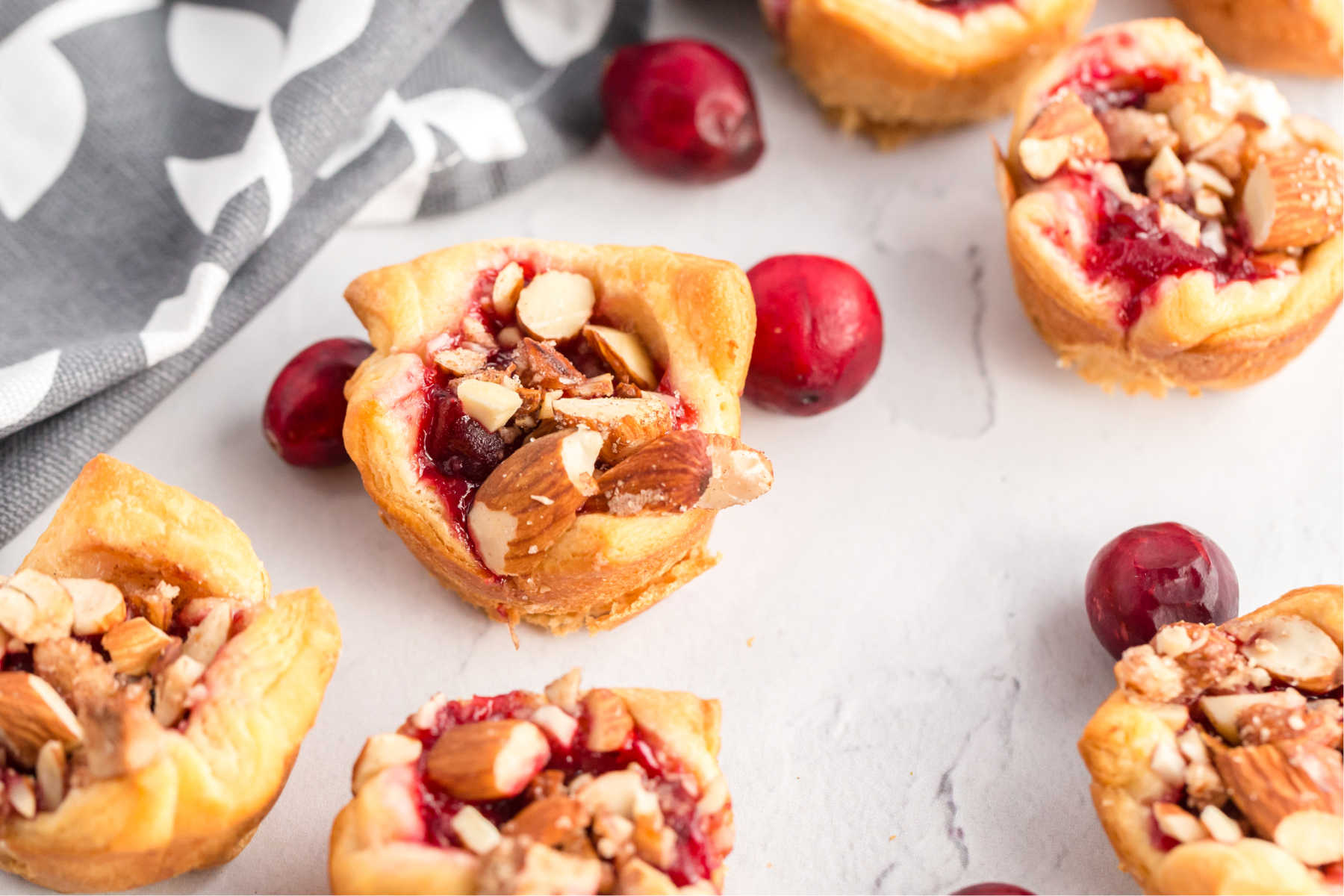 Cranberry goat cheese tarts on a table with fresh cranberries scattered.
