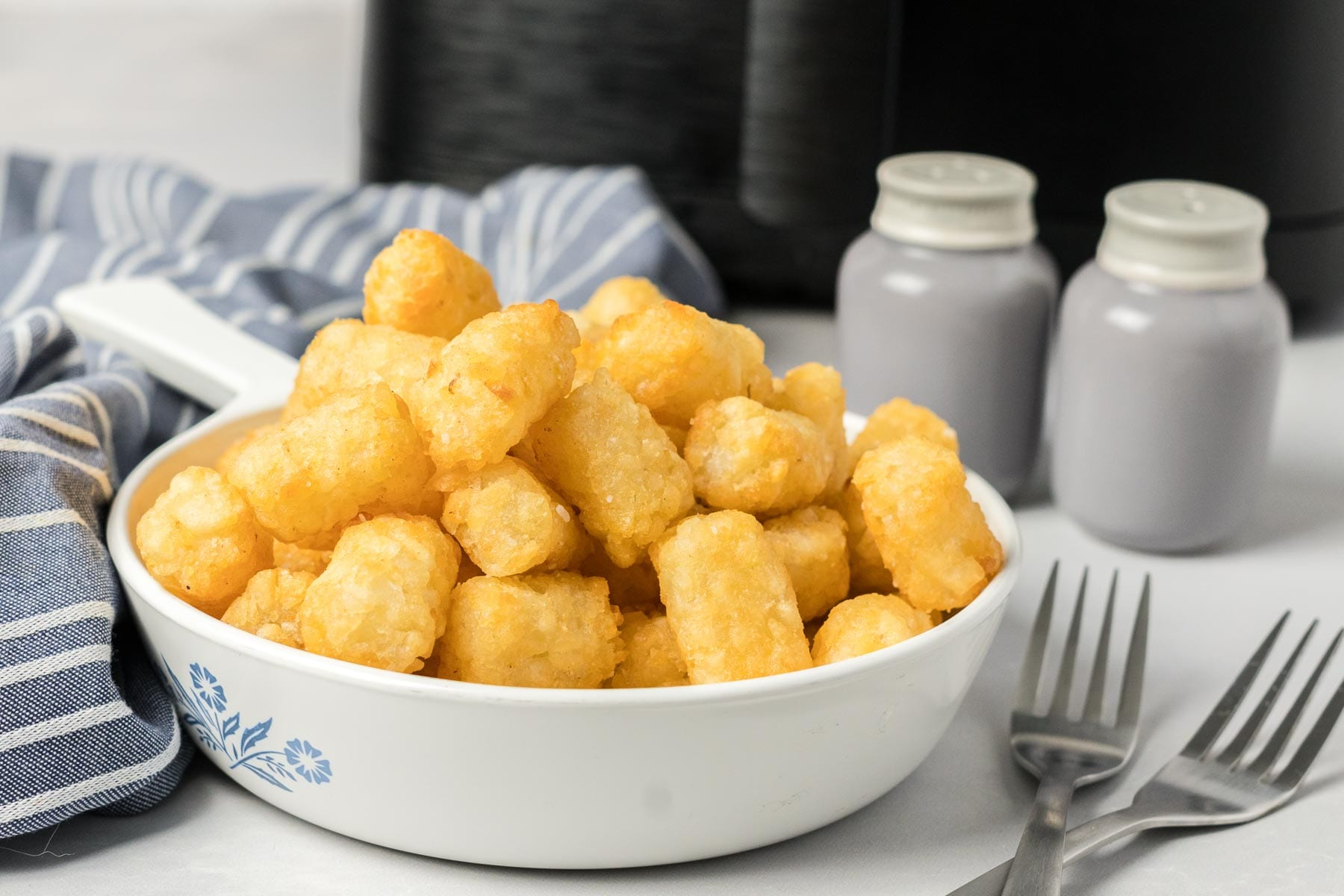 Tater tots in a bowl with salt and pepper on the side and an air fryer in the background.