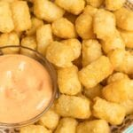 Tater tots in a bowl with spicy mayo dip.