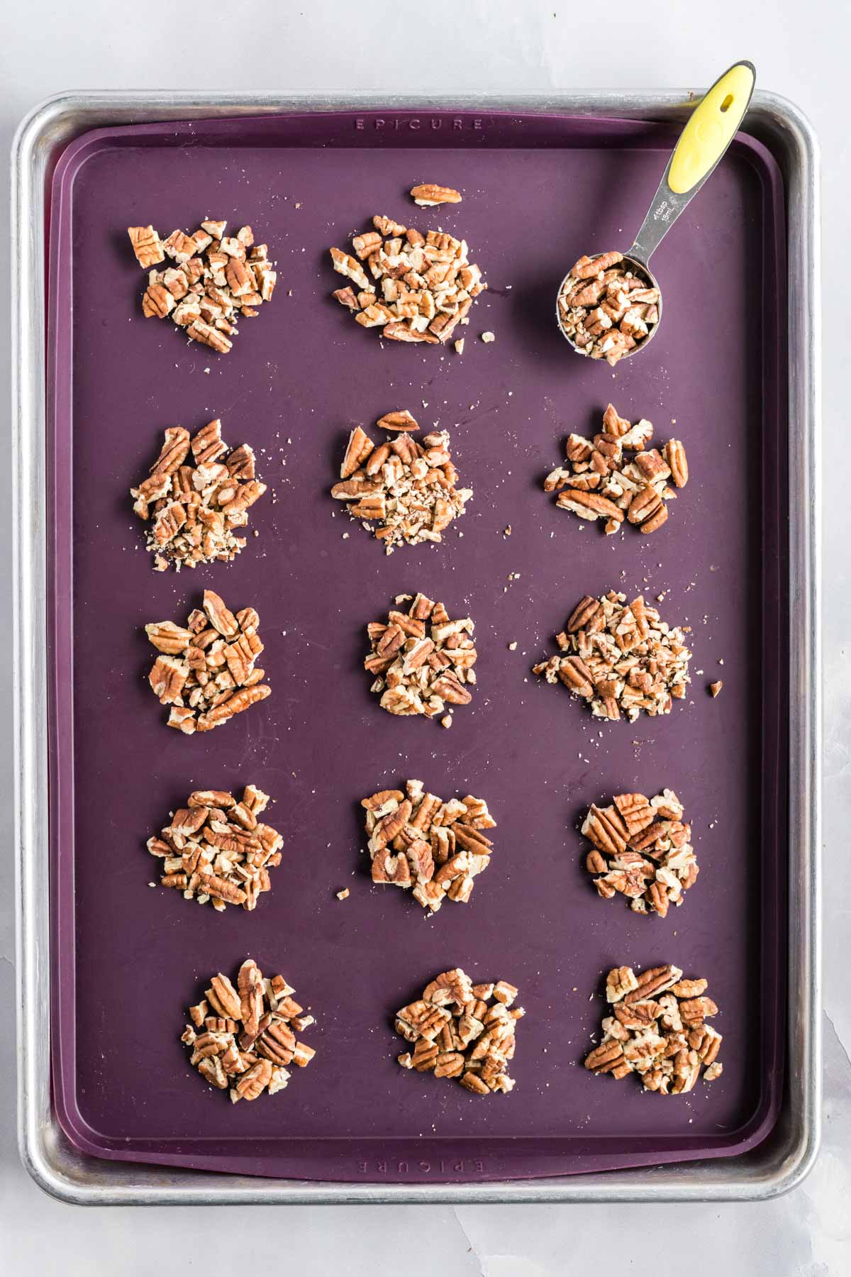 Pecans in one tablespoon piles on a baking sheet lined with a silicone mat.