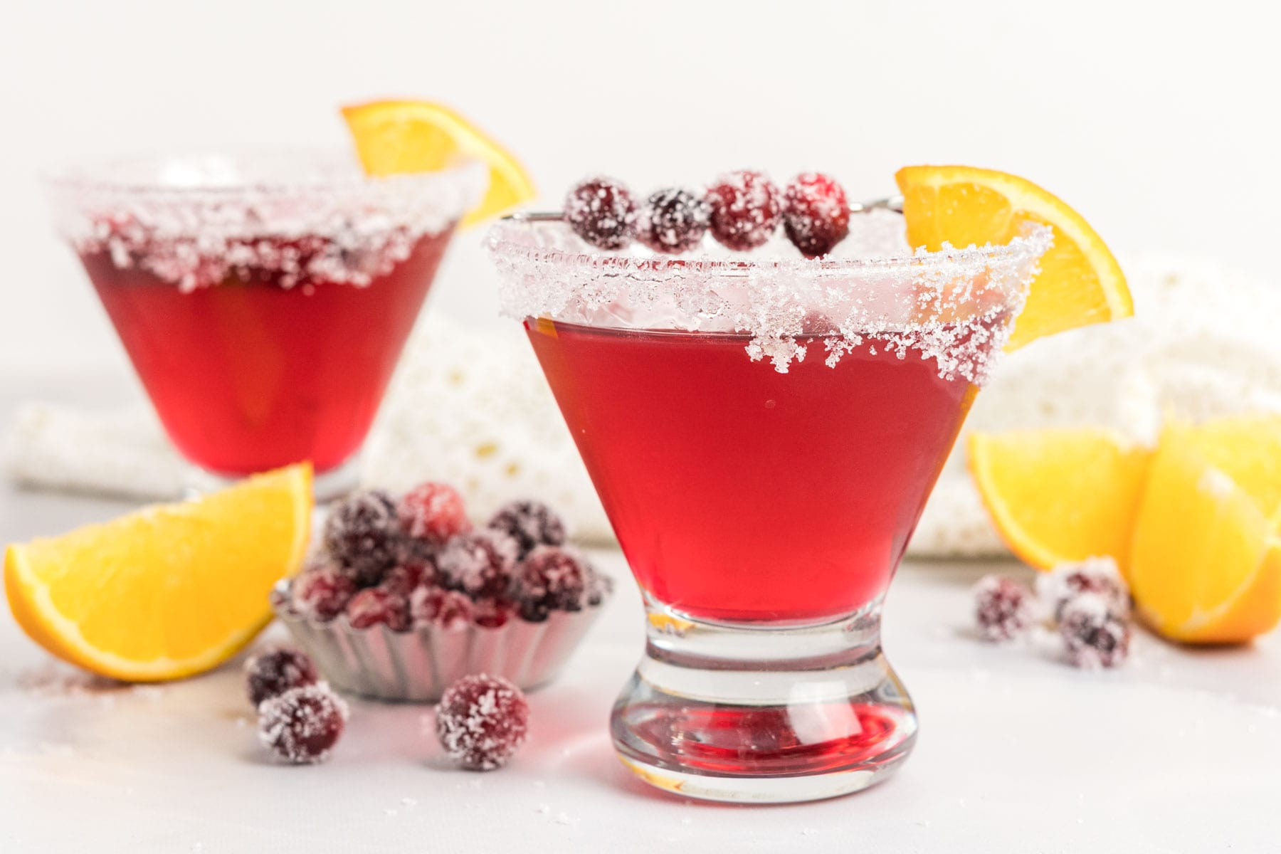 Cranberry martinis with sugared cranberries and orange sliced.