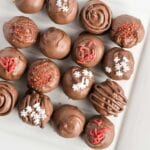 Overhead image of various decorated truffles on white platter.