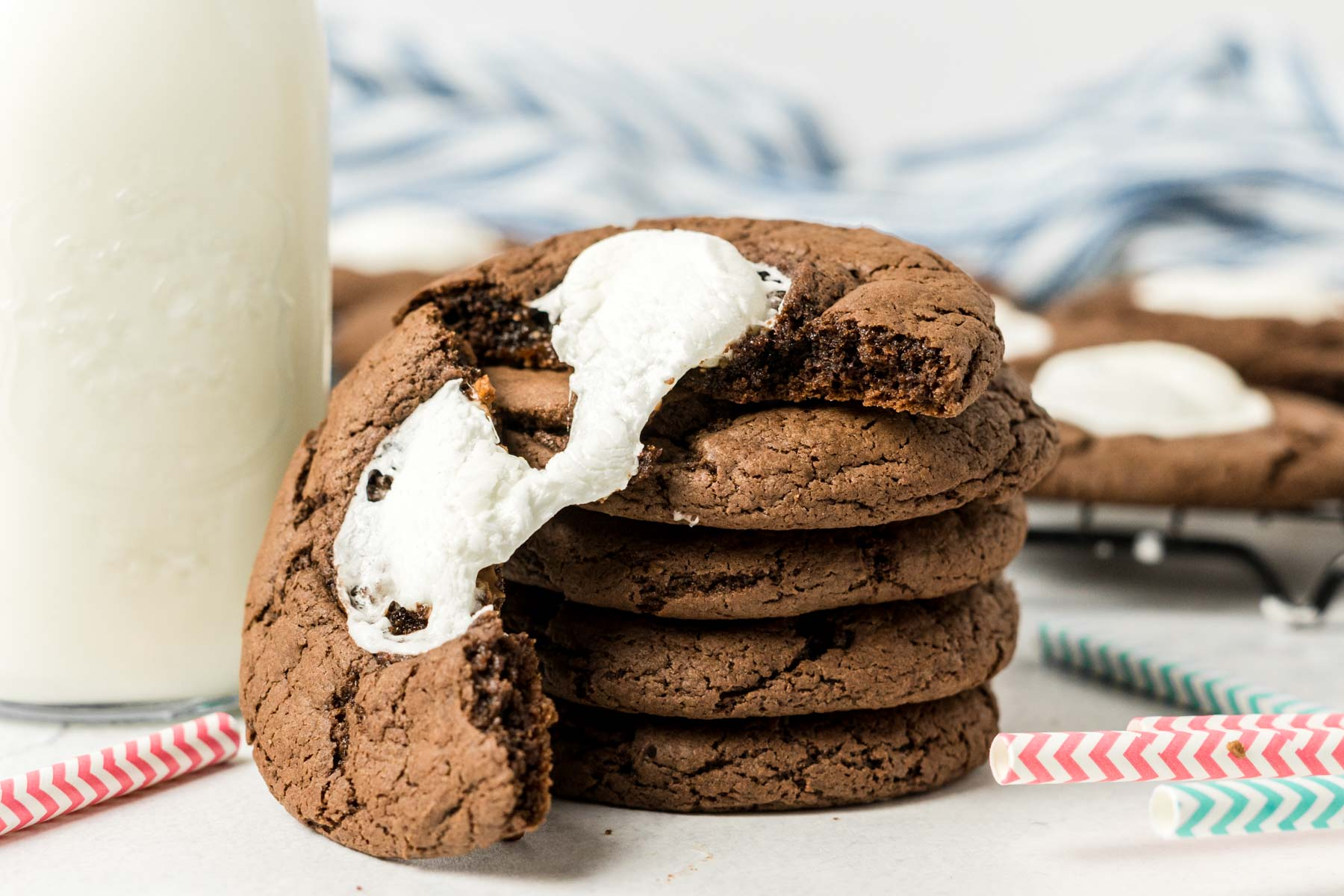 Stack of hot chocolate cookies with a bottle of milk.