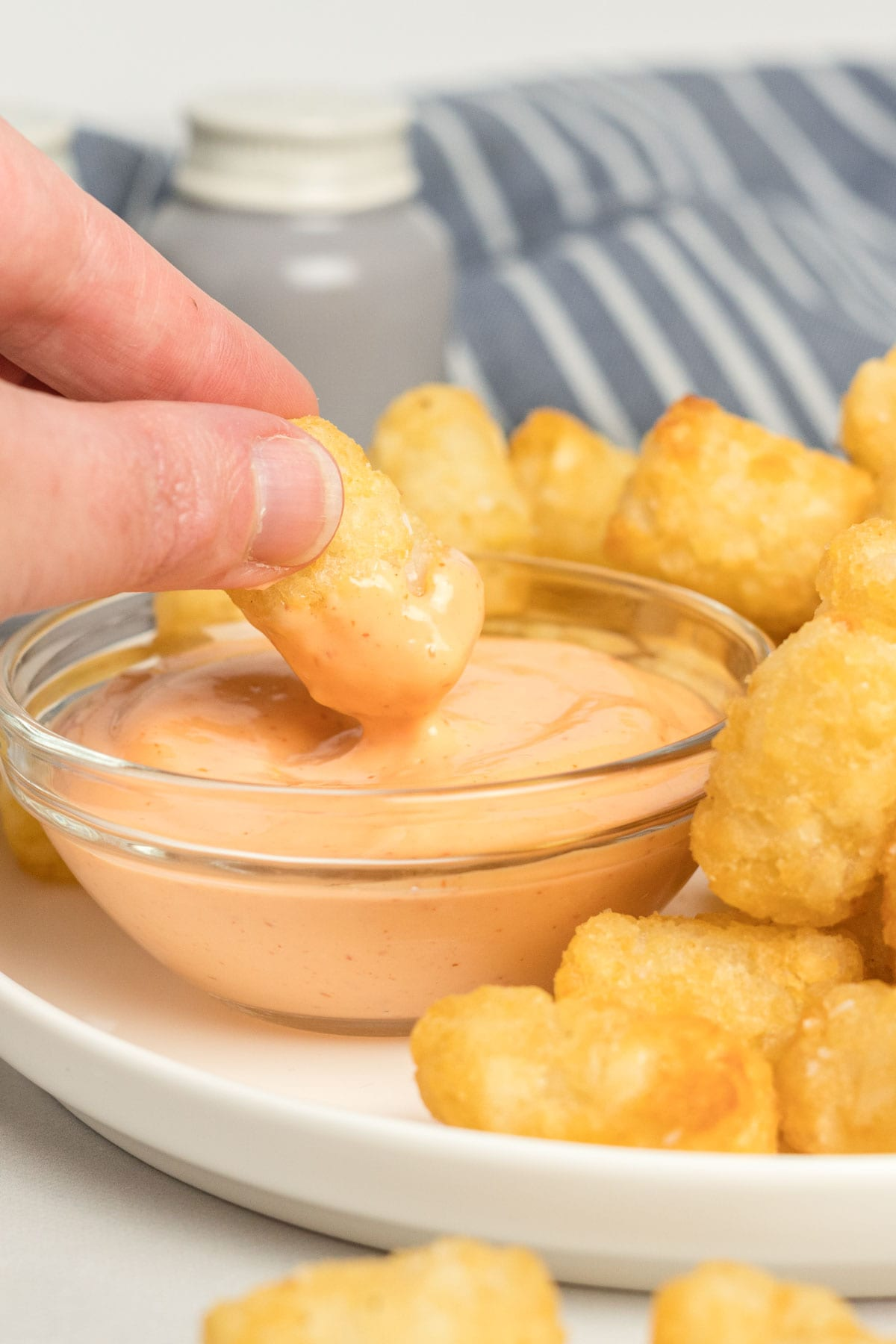 Tater tot being dipped in spicy mayo.