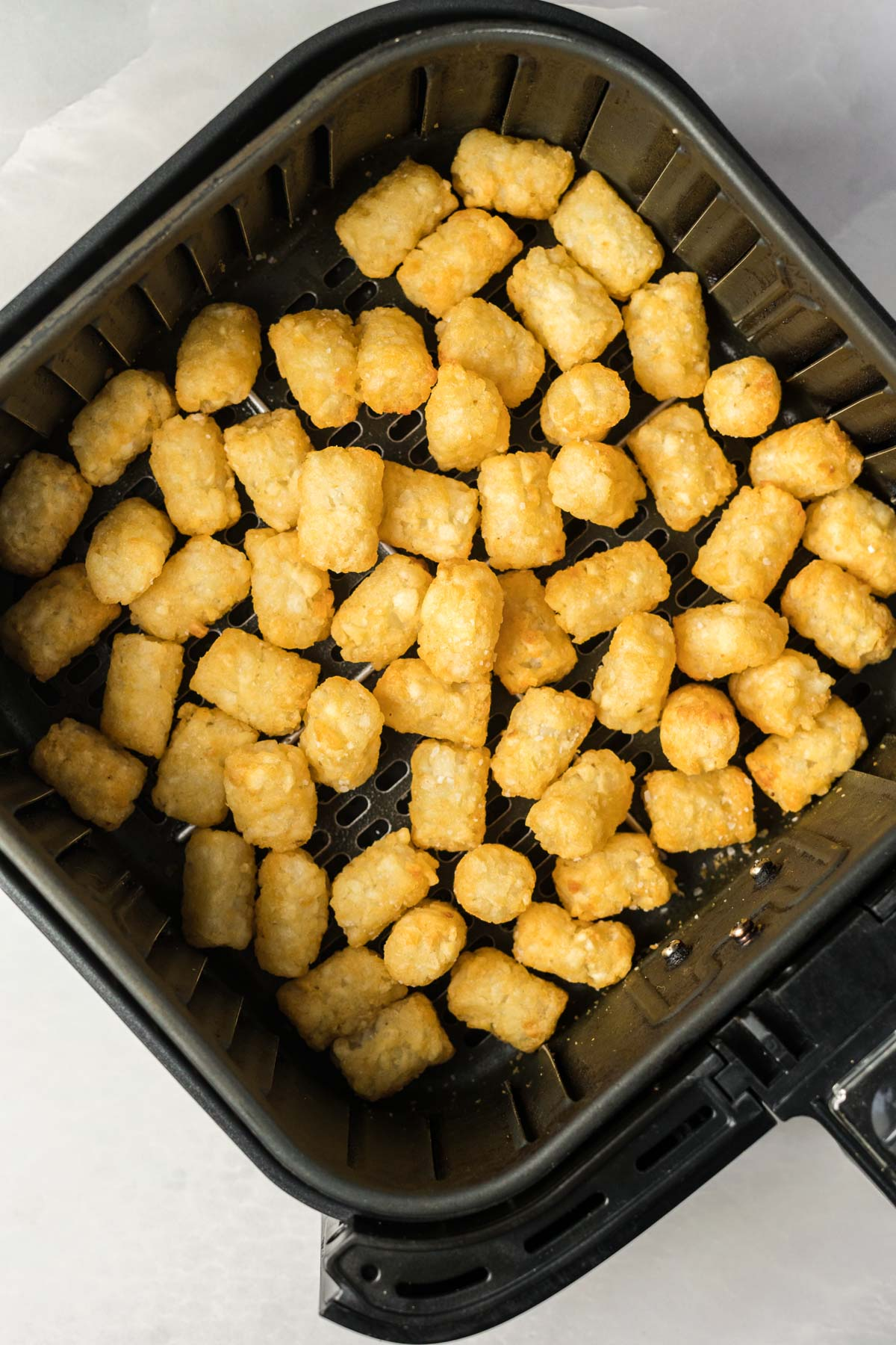 Tater tots in an air fryer basket.