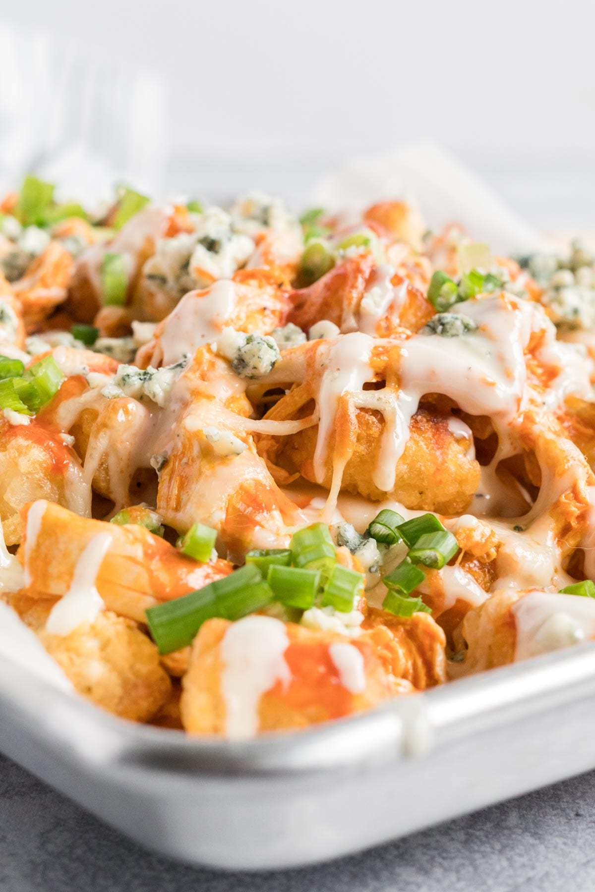 Side view of buffalo chicken totchos on a baking sheet.