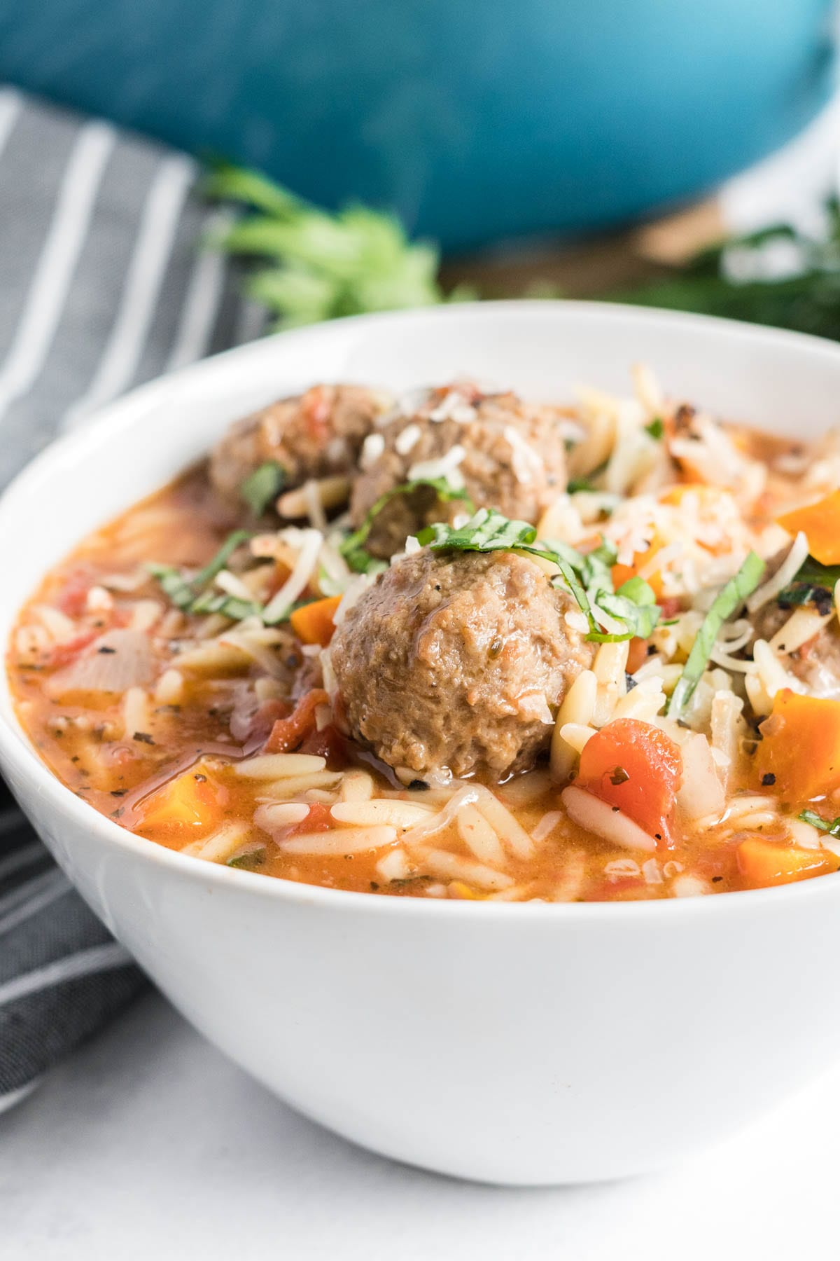 Meatball soup with orzo pasta in a deep white bowl.