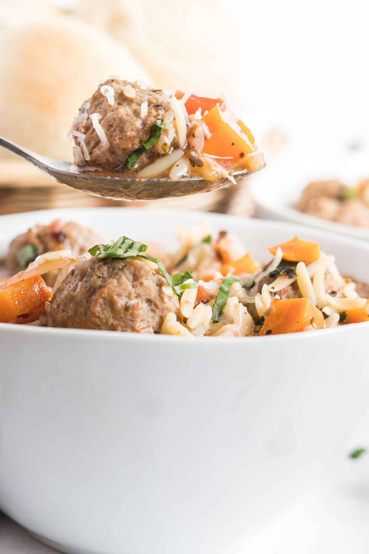 Spoonful of meatball soup with meatballs, carrots and orzo.