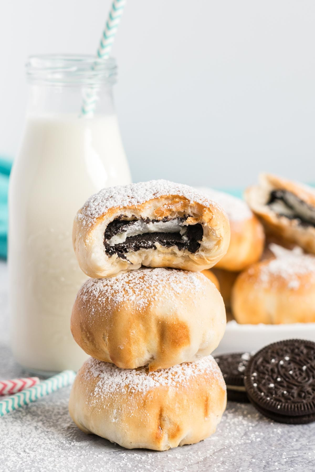 Stack of air fried Oreos and a bottle of milk with a straw.