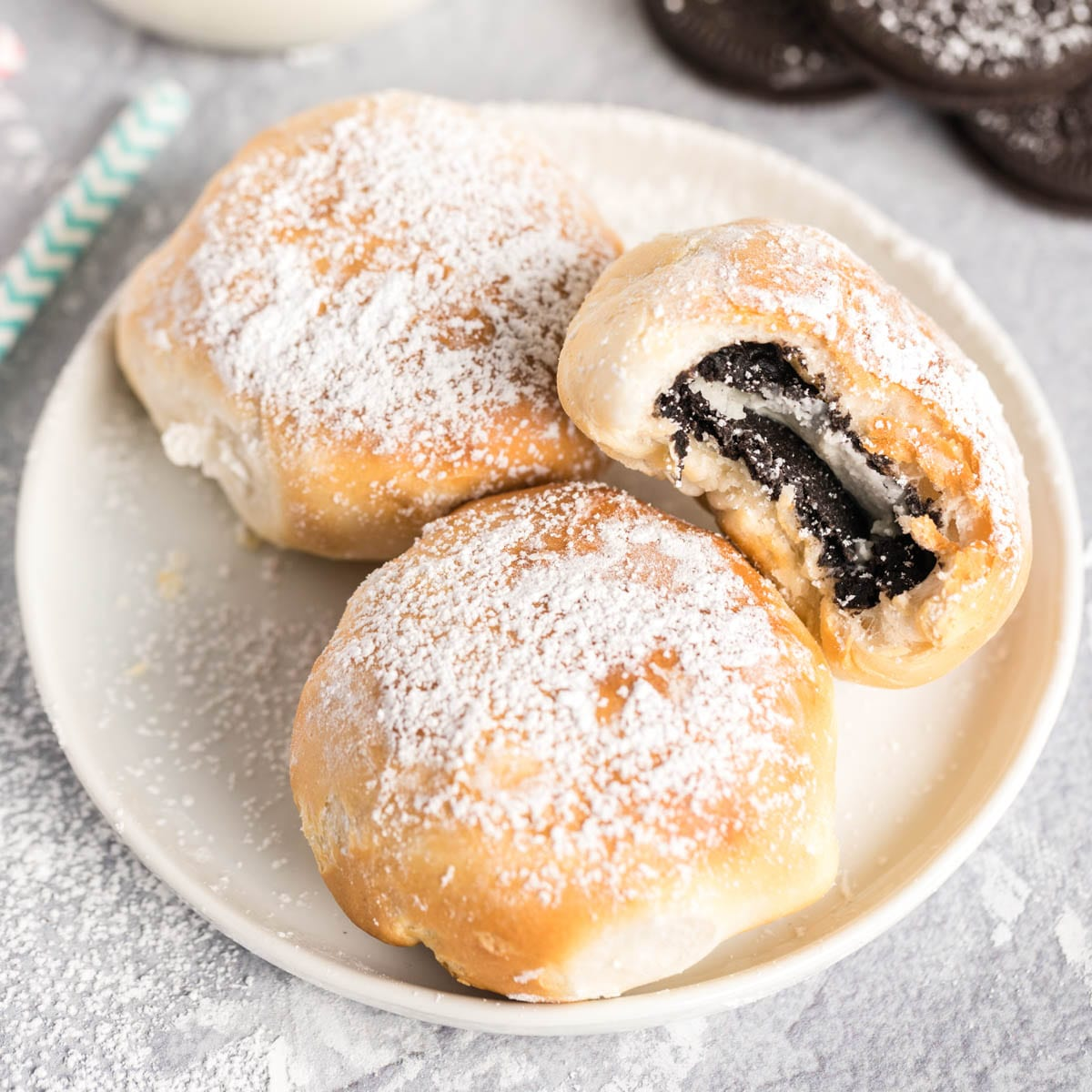 Three fried Oreos on a plate with a bite out of one.