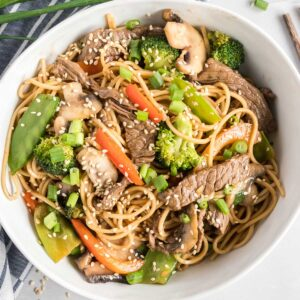 Beef, noodles and vegetables in a white bowl, garnished with sesame seeds.