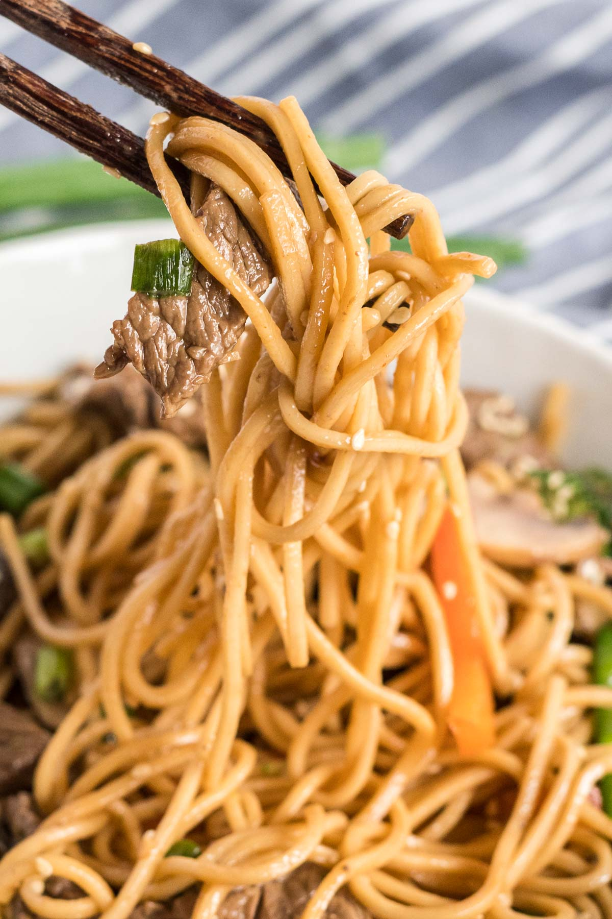 Chopsticks lifting some lo mein covered in sauce with beef strips and veggies.