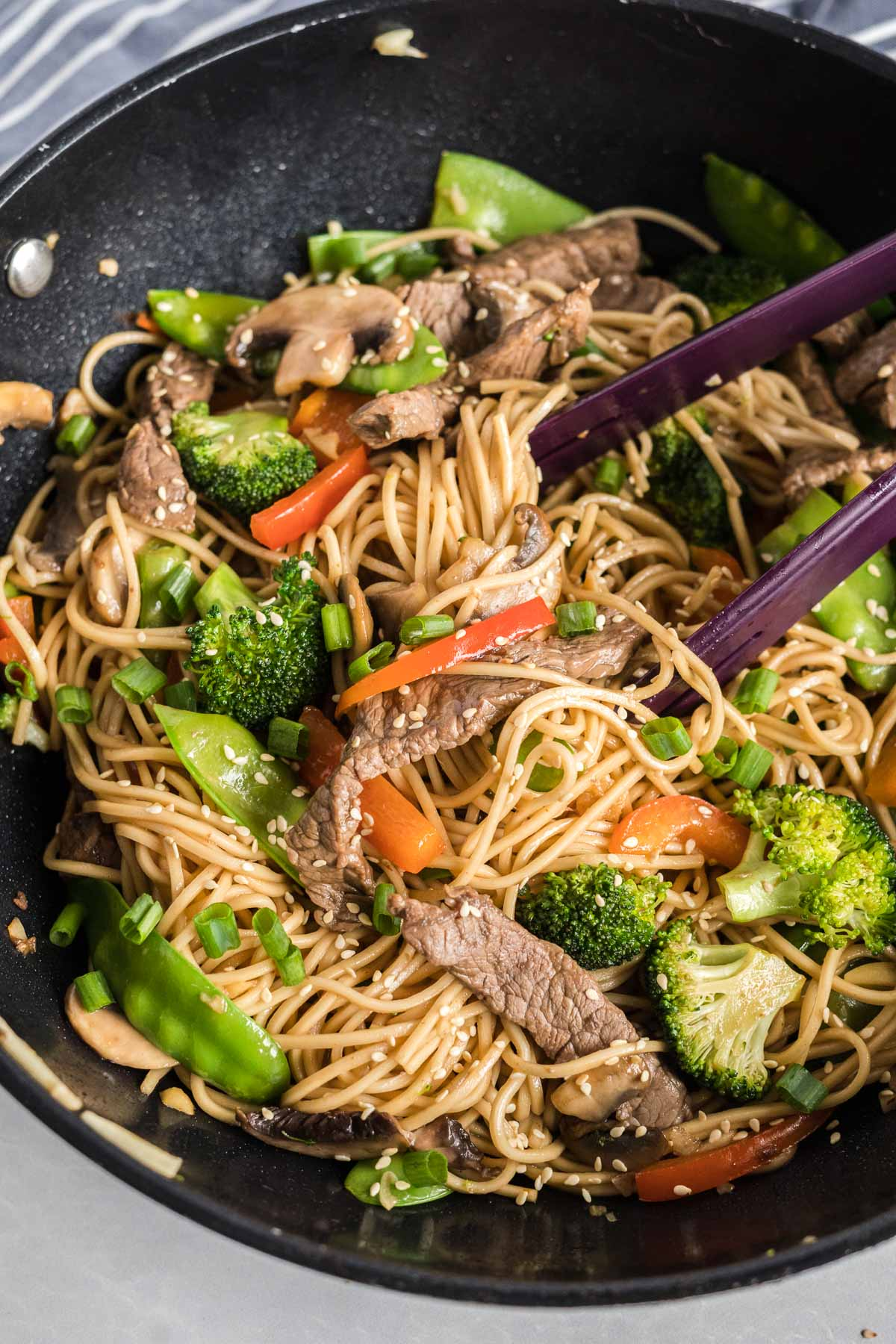 Beef, noodles and vegetables cooked in a wok with a pair of tongs for serving.