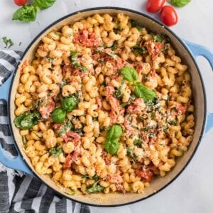 Pasta with tomatoes, feta and basil in a blue casserole dish.