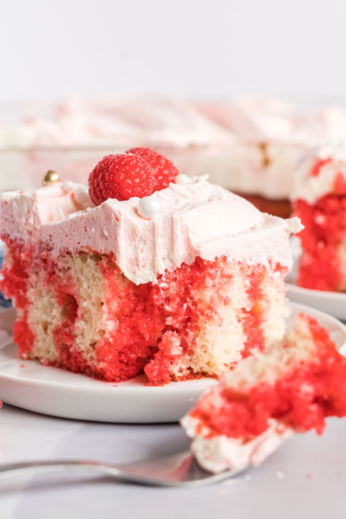 Slice of raspberry poke cake with a bite on a fork.
