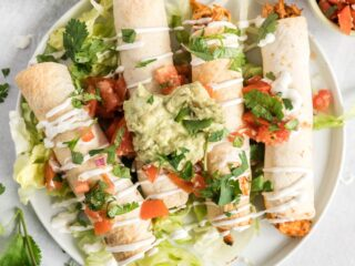 Chicken taquitos on a round plate topped with chopped tomato, guacamole and sour cream.