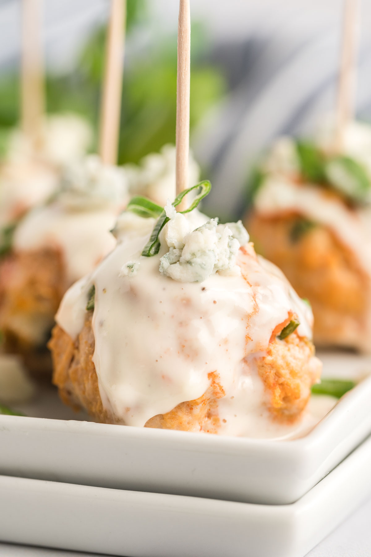 Meatball on a toothpick drizzled with blue cheese dressing, sliced green onion and crumbled blue cheese.