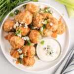 Turkey meatballs on a plate with green onion, blue cheese crumbles and hot sauce.