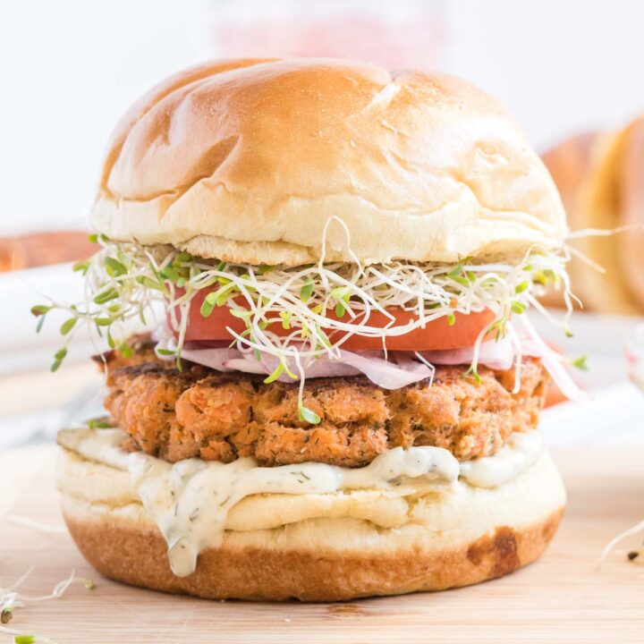 Salmon burger on brioche bun topped with tomato, sprouts and onion.