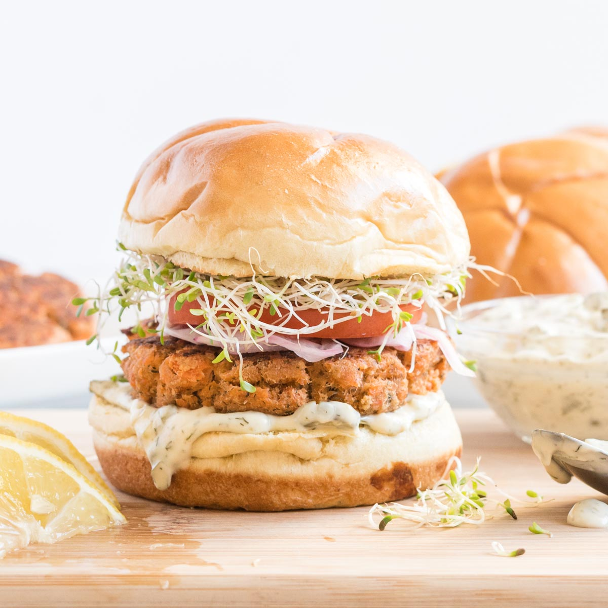 Salmon burger with onion, tomato and sprouts on a wooden board with lemon wedges.