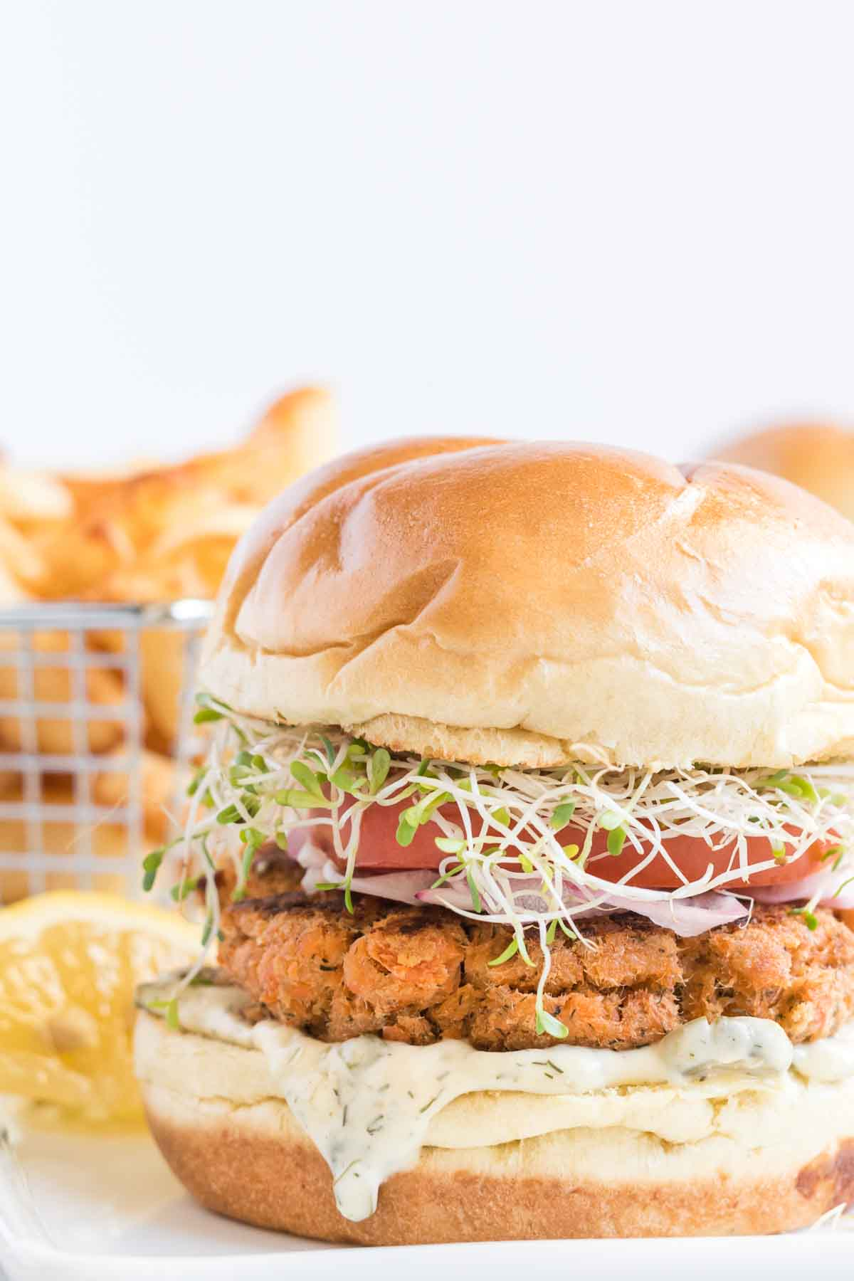 Close up of salmon burger with tartar sauce dripping out, topped with fresh veggies and french fries in the background.