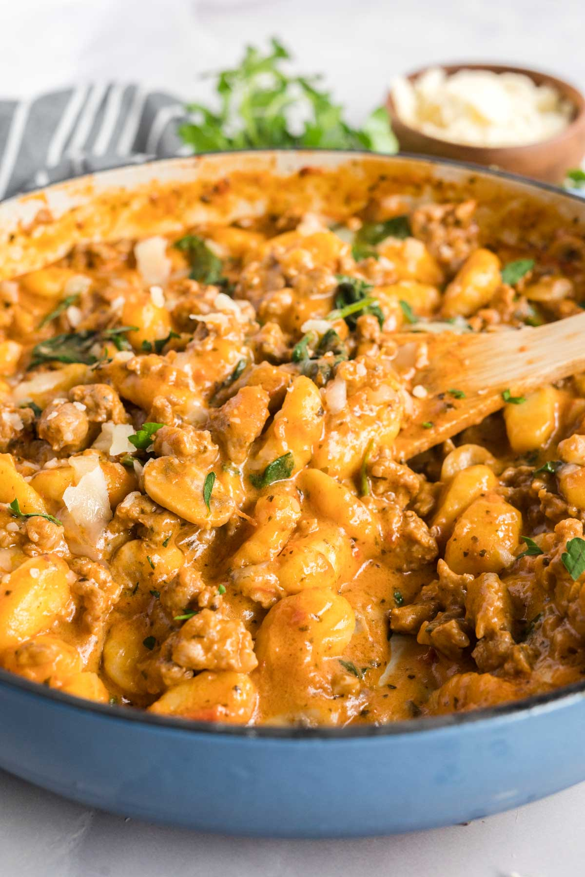 Gnocchi with red pesto sauce and Italian sausage in a blue skillet.