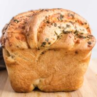 Front view of twisted cheese bread showing puffed crown and melted cheese and herbs.
