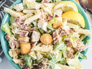 Caesar salad with chicken, bacon and pasta in a blue serving bowl.