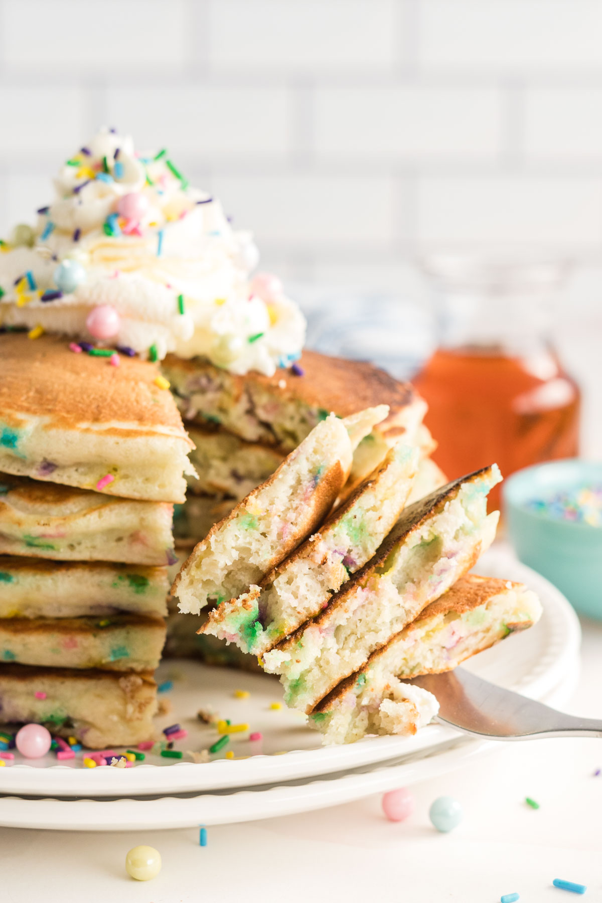 Bite of pancakes on a fork showing colourful sprinkles on inside of pancakes.