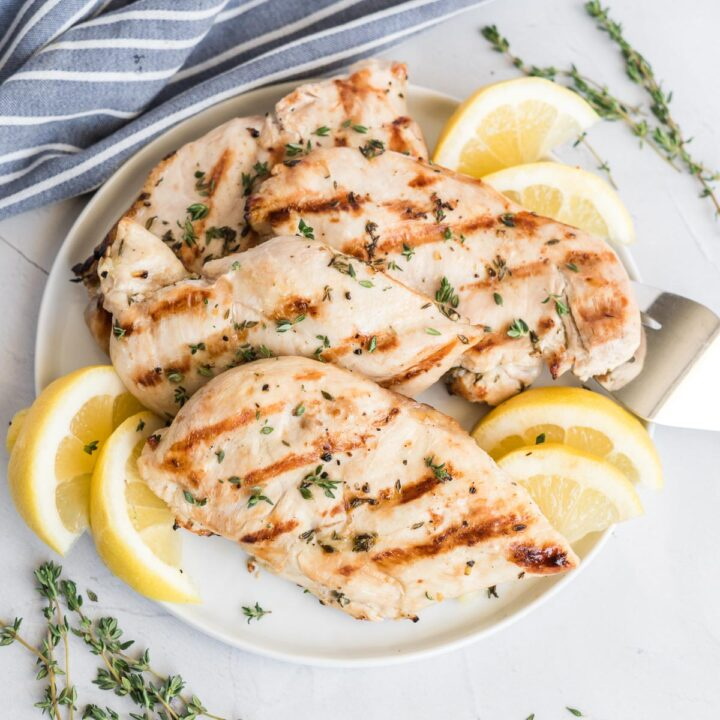 Grilled boneless skinless chicken breast on a plate with lemon wedges and fresh thyme.