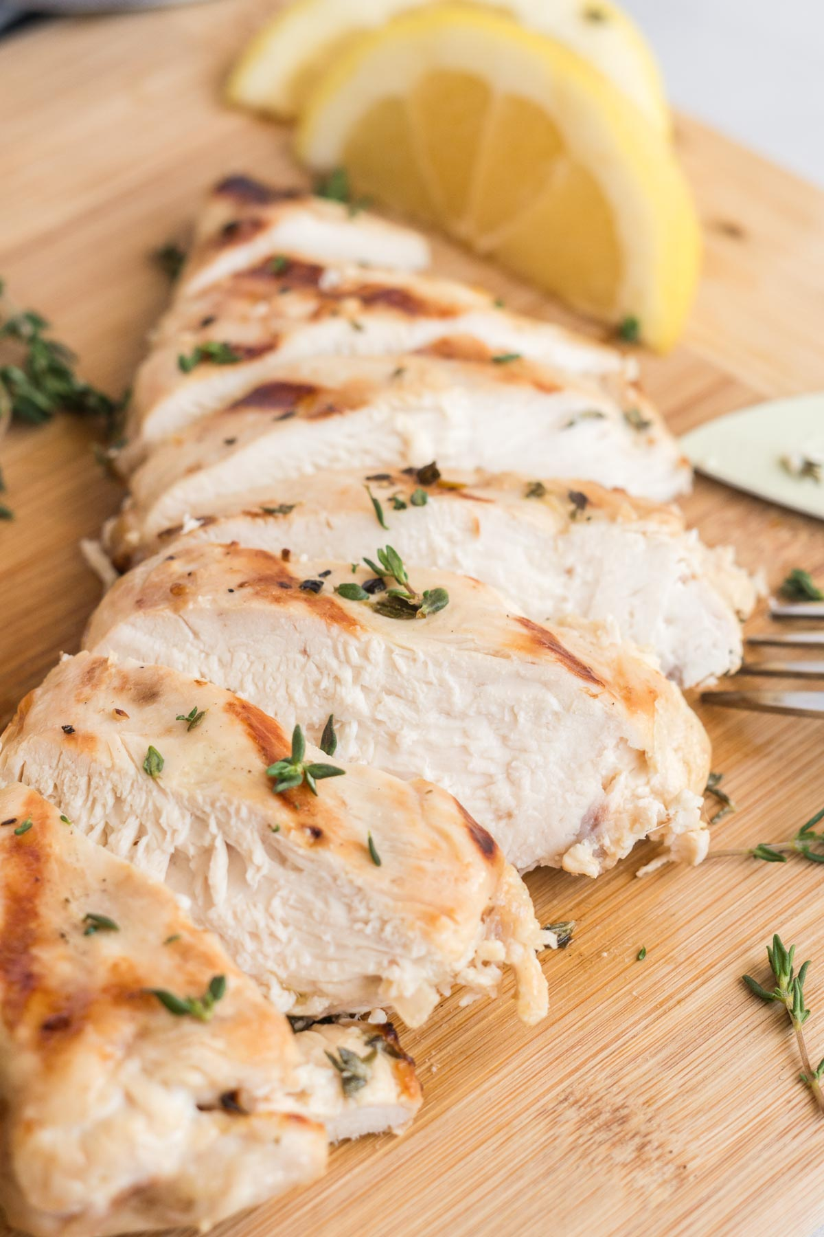 Grilled chicken breast sliced on a cutting board with lemon wedge on the side.
