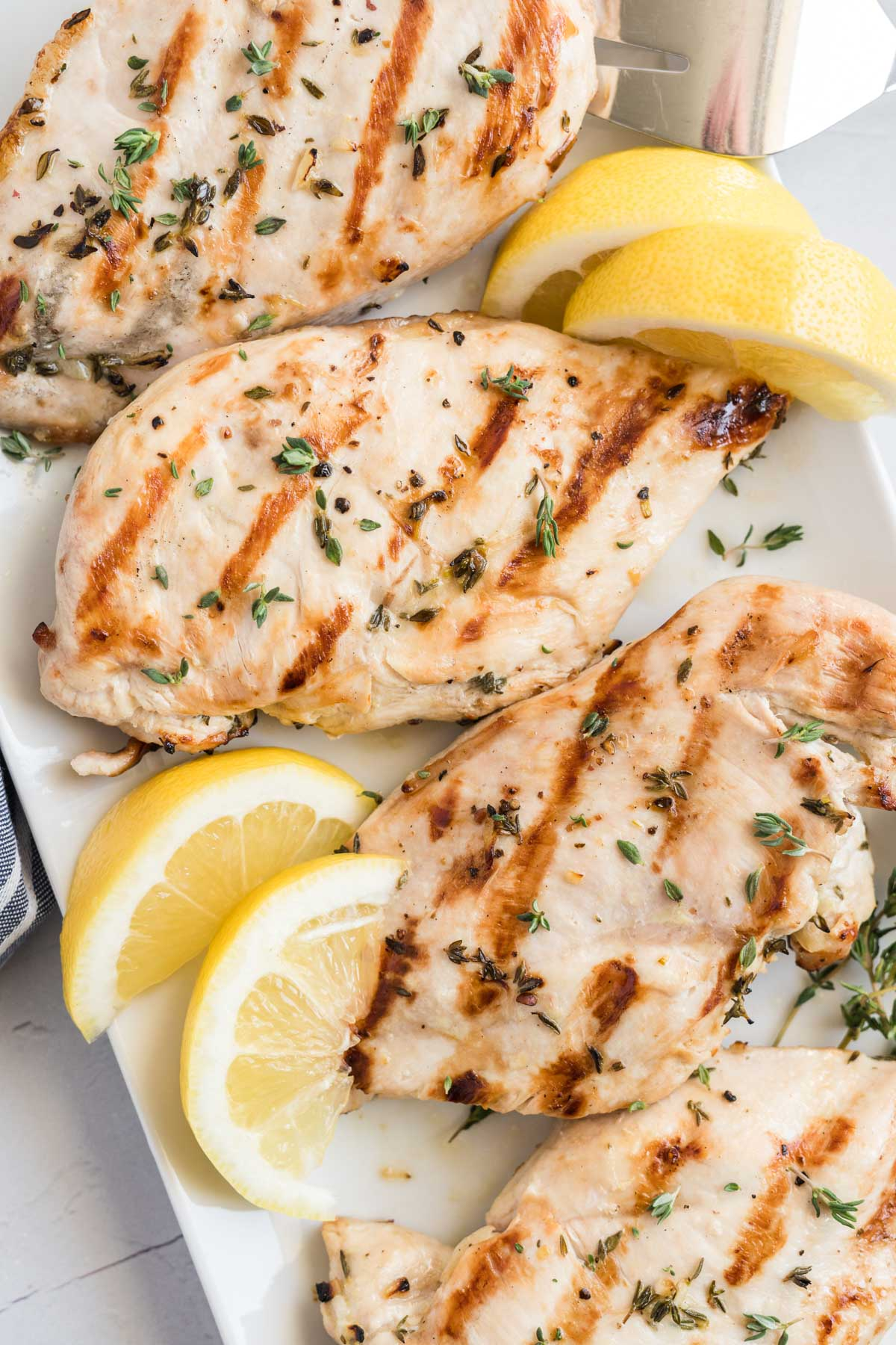 Grilled chicken on a platter with lemon wedges.