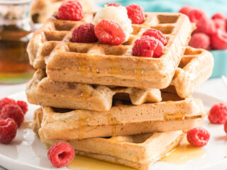 Four waffles stacked on a plate with butter, syrup and fresh raspberries.